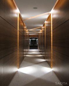 Iluminação indireta, com LED e cores frias. Muito bem trabalhado! Fez com que o ambiente oferecesse mais do que um simples corredor. Uma graça!