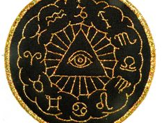 Eye of the Zodiac features an all seeing eye in the center of the zodiac symbols. It is stitched on black twill with gold mylar threads, and measures