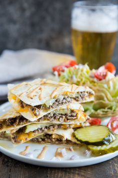 A photo taken at slight downward angle of a stack of cheeseburger quesadillas on a white plate. A wedge of iceberg lettuce with tomatoes and pickles are on the side. A glass of beer is in the back.