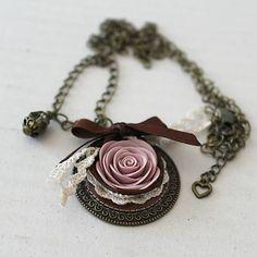 Ručne modelovaná ruža z polyméru s lupienkami v jemných odtieňoch staroružovej farby na vintage lôžku ozdobenom hnedou mašličkou a béžovou čipkou, so staromosadznou retiazkou ozdobenou korálkou s pokovom, zapínanie s karabinkou.