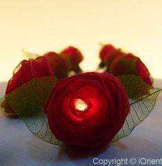 Ribbon roses made of gauze  and lacy leaves, en-wrap   white lights to beckon fairies.