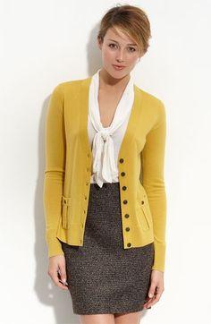 La muchacha lleva una blusa blanca y falda gris y saco amarillo