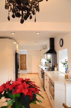 White kitchen, black range and fridge, blue glass splashback