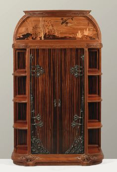 Louis Majorelle                              1859 - 1926                              CABINET LA MER, VERS 1905                              LA MER, A MAHOGANY, COURBARIL, MARQUETRY INLAID AND WROUGHT IRON CABINET BY LOUIS MAJORELLE, CIRCA 1905. SIGNED