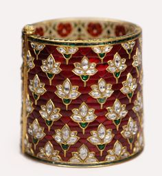 Cuff Bracelet set with calibrated rubies, emeralds and diamonds. Traditional Indian motifs enamelled on gold on the inside. From the Traditional Mughal Collection.