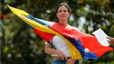 Opposition leader Maria Corina Machado holds a Venezuelan flag during a women's protest outside the Bolivarian National Guard headquarters i...