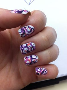 White base with colors laid down using a drinking straw dipped into polish and dabbing that to the nails.