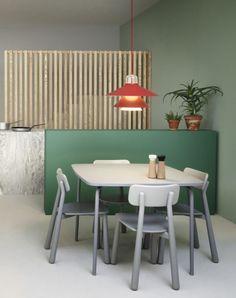 A modern table setting. Orange pendant light, green interior