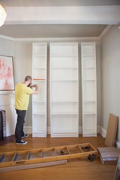 Ikea Billy Bookcases ($40-$60) of various sizes are assembled together to create the three columns of the built-ins. #DIY
