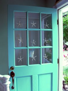 Blue beach house door with star fish accents on the window panes. #beachhouse