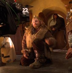Fili catching plates. What on earth is Kili doing in the background? Is he sitting in the doorway off the ground?
