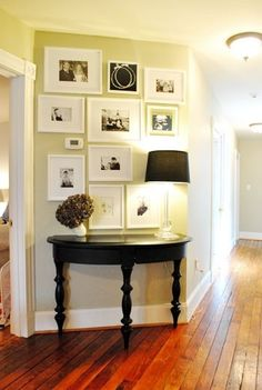 black and white wedding photo gallery above the console table in the entryway