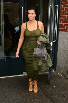 In an army green tank dress and matching jacket   - HarpersBAZAAR.com