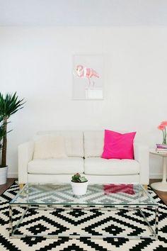 sofá branco na decoração da sala de estar com almofada rosa pink, tapete preto e branco e mesa de centro de vidro