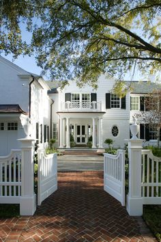 Classic white exterior with black shutters, brick walkway