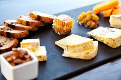 Fancy cheese plate with blue cheese, cheddar, goat cheese, bread, honey and pistachios at a luxury restaurant.  Horizontal shot. High angle view.