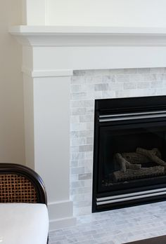 White & Marble Fireplace (The Makeover Details) - Satori Design for Living - - Our fireplace makeover is officially done! Come check out how we used inexpensive trim, white paint and marble subway tile to give it a fresh new look. Subway Tile Fireplace, Herringbone Fireplace, Fireplace Tile Surround, Fireplace Update, Fireplace Hearth, Marble Fireplaces, Fireplace Remodel, Fireplace Inserts, Fireplace Surrounds