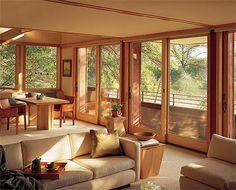 Grandes paineis de vidro, e a luz solar entra abundante. As cores usadas, as cores da terra, a madeira que traz aconchego, tudo faz o ambiente ser perfeito. anderson sliding glass doors patio living room