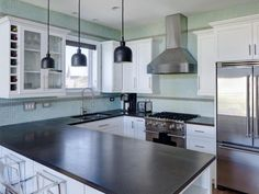 Appliances: Modern Kitchen With Aqua‐Blue Tile Backsplash And White Cabinetry. black kitchen appliances. black food processor. black pendant light. stainless steel gas range. stainless steel range hood. white kitchen cabinet. dark countertop. stainles steel refrigerator. mosaic backsplash. clear acrylic barstools.