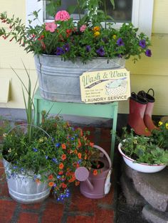 Summer flowers in a vintage wash tub surrounded by  rubber boots, galvanized pail and watering can!.