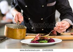 Chef in hotel or restaurant kitchen cooking, only hands, he is working on the sauce for the food as saucier, a Risotto