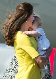 In mummy's arms: A sleep George snuggles up to mother Kate as they leave the aircraft, before he was cared for by his nanny
