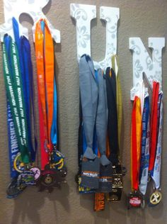 DIY medal display: pre-made letters, decorative paper, key hooks. You could make any word, or year (maybe for high school graduation).