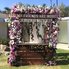 "The Zoe Report & Dolce Vita Pool Party: Flowers and vines covered a kissing booth photo station emblazoned with the message ""All my friends are models."""