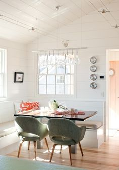 love this light and airy eating nook, lofty ceilings, white and green and orange accent.