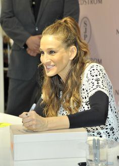 SJP signs shoe boxes for customers at her LA event.