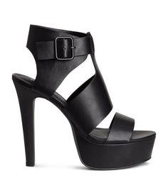 Black. Platform sandals in imitation leather. Adjustable, elasticized ankle section with metal buckle. Imitation leather insoles and rubber soles. Front