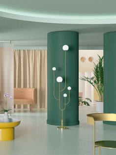 séparation chambre salon avec des colonnes en couleur vive, vert, colonnes en formes ovales, carrelage blanc, canapé rose, fauteuil en métal doré, table basse ronde en jaune