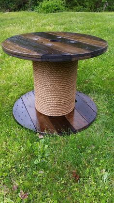 Wooden wire spool table! The table is stained, coated with polyurethane, and the base is wrapped with rope. The table is 2 ft tall x 2.5 ft wide. Great piece for an indoor or outdoor table