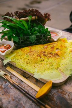 """Banh Xeo.""  A thin, crispy, very light pancake filled with pork, prawn and veggies. Served with herbs, fish sauce, chilli sauce and lettuce."