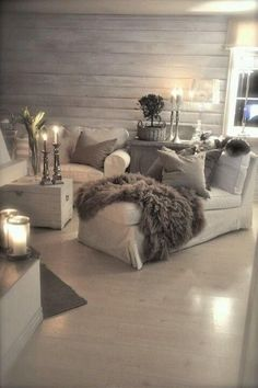 Living room colors. Cream blankets, dresser, candle holders with cream candles, lanterns, gray curtains, bottom wall gray distressed wood.
