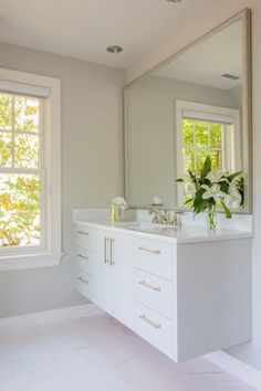 Chic bathroom features a white floating vanity accented with antiqued nickel pulls alongside a sleek white counter which frames a rectangular undermount sink and an antiqued nickel  faucet under a champagne silver vanity mirror over gray walls alongside white marble tiled floors.