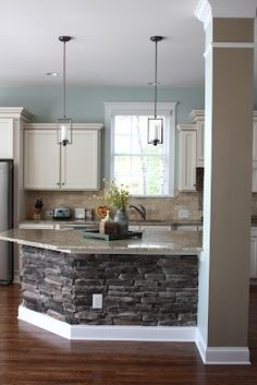 Kitchen. Pretty dark wood floors, light blue and brown walls. Stone accent under bar also prevents scuff marks.