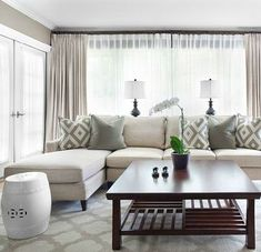 Mark Williams Design Gorgeous monochromatic living room design with gray walls paint color, ivory sofa with chaise lounge, David Hicks La Florentina pillows, gray pillows, white garden stool, cherry square table, blue lamps, oatmeal linen window panels cu...