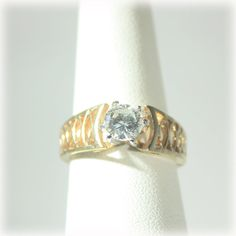 Pierced metal build up with a large open back and prong set clear rhinestone. High facet count give this ring a lot of sparkle.    Material: 18k