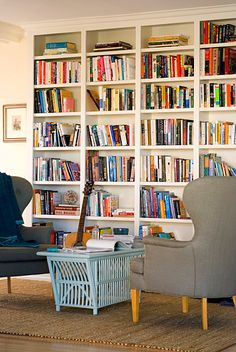 I like the high backed chairs and the blue table in this home library.