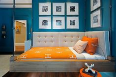 Blue boy's bedroom boasts walls painted peacock blue lined with a wood and metal bed suspended from the ceiling dressed in an orange Hermes Avalon Blanket.