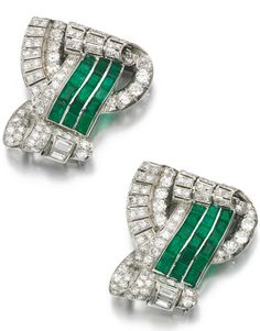 EMERALD AND DIAMOND DOUBLE CLIP BROOCH, 1930S Each of scroll design, set with calibré-cut emeralds, circular-, single-cut and baguette diamonds.