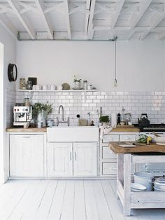 pretty much everything i want in a kitchen! white kitchen bare bulbs subway tiles white floor boards rustic bench tops the tapware the black french school clock!----ugliest kitchen ever idk how this could b a dream kitchen. Kitchen Interior, Kitchen Inspirations, Top Kitchen Trends, Kitchen Trends, Kitchen Remodel, Kitchen Decor, New Kitchen, Country Kitchen Designs, Home Kitchens