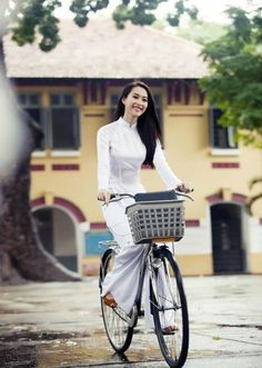 Ao dai Vietnam: Vietnamese girl in white ao dai on a bicycle