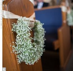 a cute idea for dressing pews for the ceremony - a baby's breath wreath and a satin ribbon