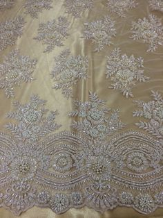 White beaded lace fabric with gold lining