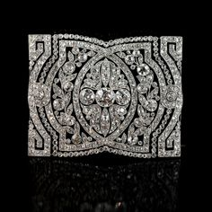 Beautiful Belle-Epoque articulated collar-piece of rectangular form with three central old-European cut diamonds within an openwork panel of diamond-set garlands and stylised geometric details circa 1905
