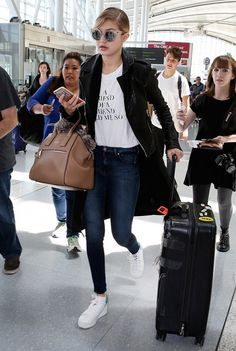 Gigi Hadid wears a graphic t-shirt, motorcycle jacket, skinny jeans, and white platform sneakers