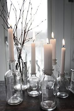 lots of creamy candles held in clear glass bottles Candle Lanterns, Diy Candles, White Candles, Mason Jar Crafts, Mason Jars, Light Decorations, Christmas Decorations, Table Decorations, Candle In The Wind