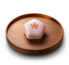 Sakura gata (Cherry blossom shaped) - A sakura blossom is pressed with abranding iron on a pentagon shaped cake - its angles looking like the flowers 5 petals.  The faint pink hue, seen throught the rice paste, brings to our memory the scenery of spring hills covered in cherry blossoms.  [personnal translation]